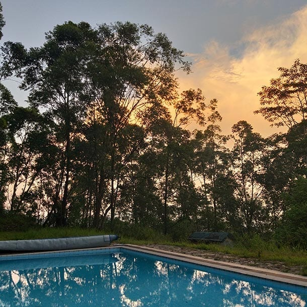 Swimming pool at sunset with the sky reflected at Jungle Tide hotel Kandy Sri Lanka